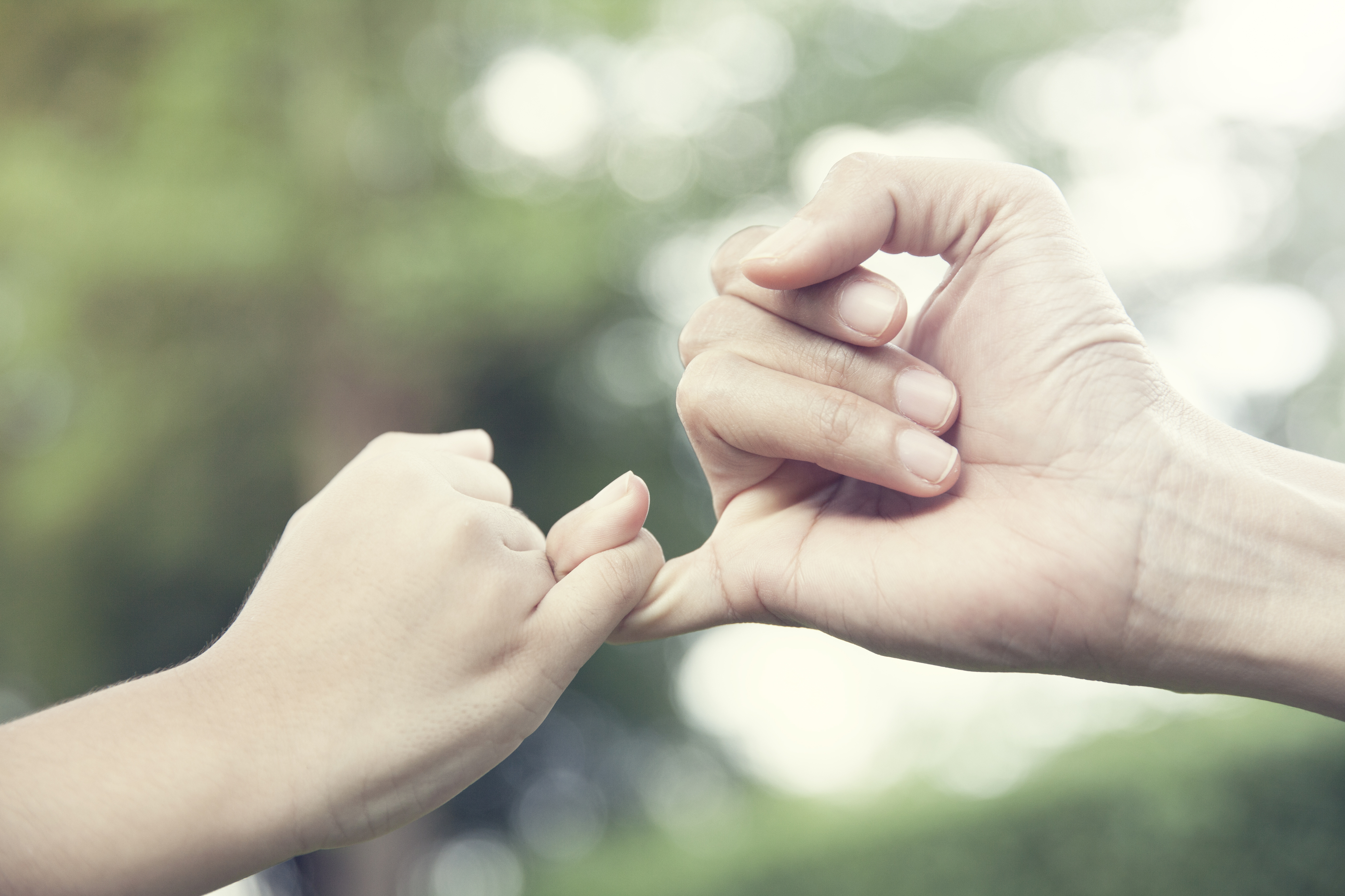 mother and her child hooking their fingers to make a promise